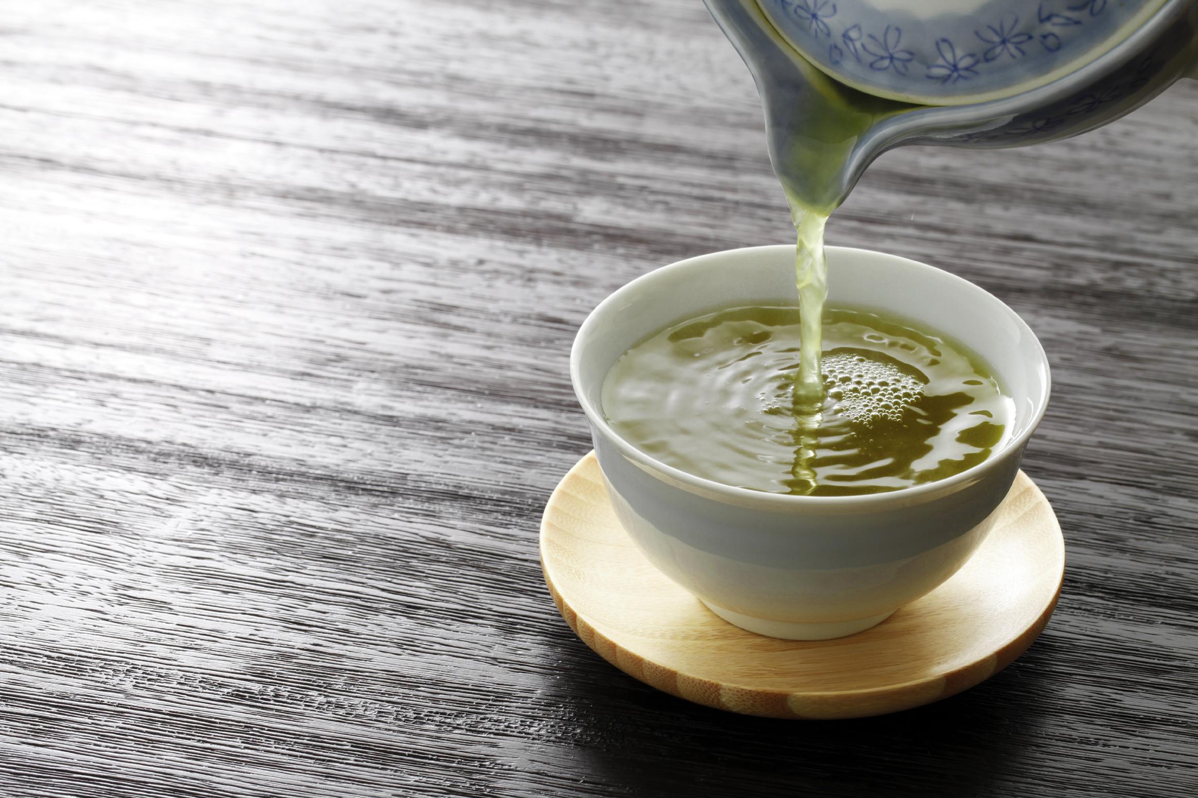 Tetera vertiendo té verde